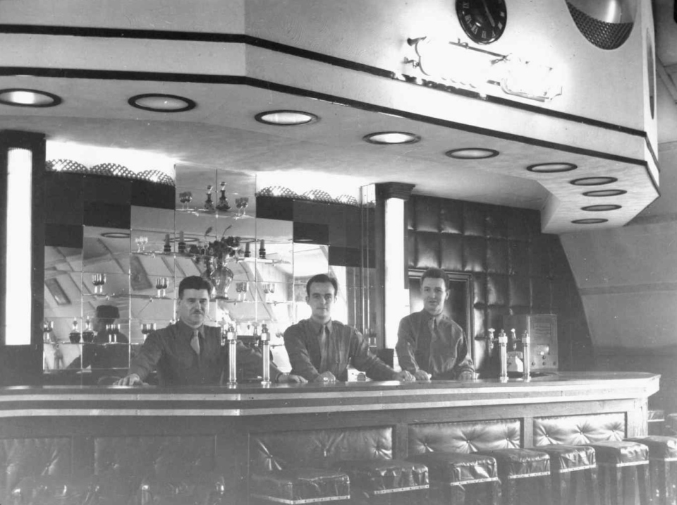 The bar of the 384th Bomb Group Officers' Club. Bartender Primo Lombardi on the left.